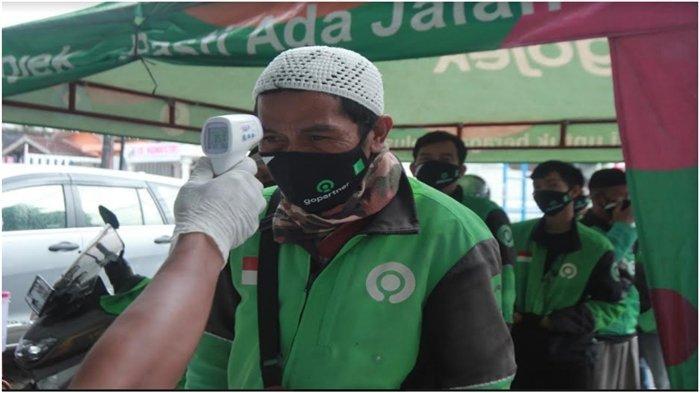 Mitra driver Gojek diukur suhu tubuhnya.