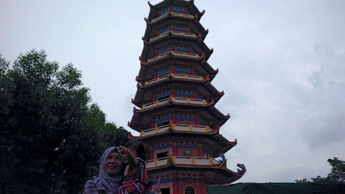 Warga foto dengan latar belakang Pagoda di Pulau Kemaro, Minggu beberapa waktu lalu.