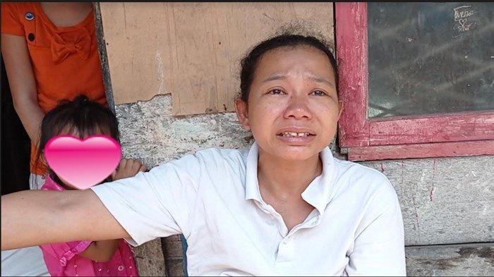 Uyet (32) tak kuasa menahan tangis saat menceritakan kebingungan yang harus dihadapi keluarganya karena handphone untuk belajar daring anaknya kini hilang dijambret orang tepat di depan kediamannya, Senin (19/7/2021).