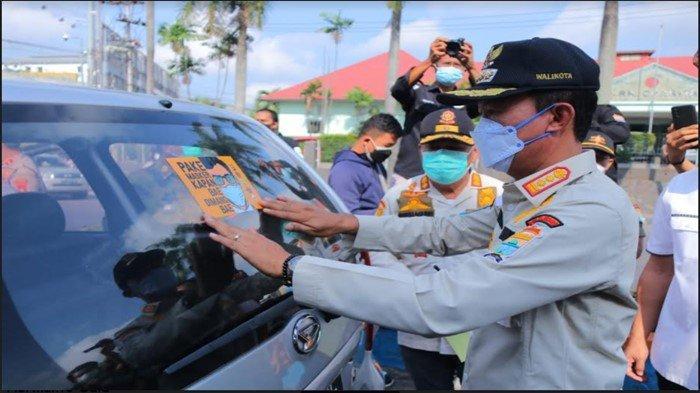 Turun Ke jalan, Walikota Palembang Harnojoyo Pasang Stiker Ajakan Patuh Prokes