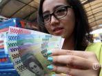 warga-menunjukkan-uang-kertas-rupiah-baru-tahun-emisi-2016_20161220_143915.jpg