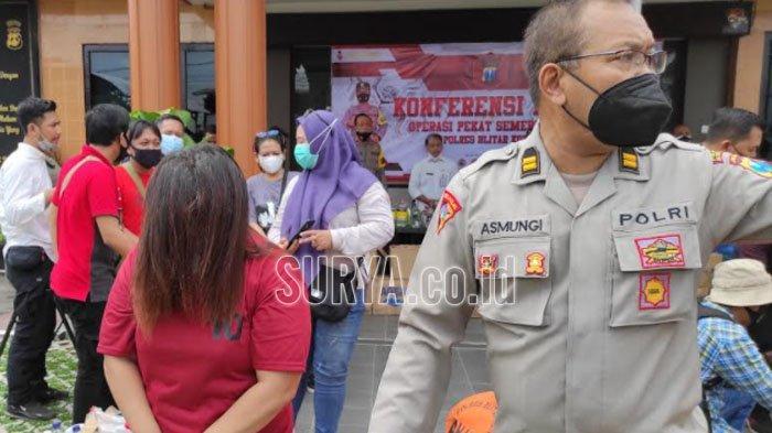 BY (40), muncikari prostitusi online anak di bawah umur saat hendak dibawa ke sel tahanan Polres Blitar Kota, Rabu (7/4/2021).