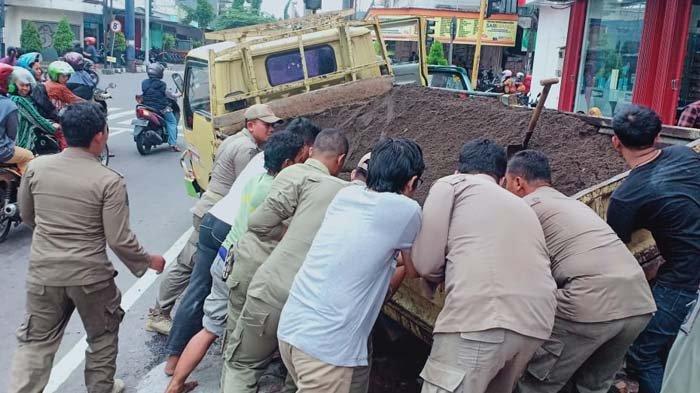 Dump Truk Terperosok Lubang di Jalan Patimura Kediri, Warga Gotong-Royong Mengangkat