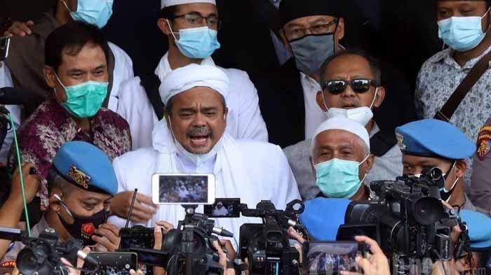 Pemimpin Front Pembela Islam (FPI), Muhammad Rizieq Shihab didampingi kuasa hukumnya, Munarman tiba di Mapolda Metro Jaya, Jakarta Selatan, Sabtu (12/12/2020). Kedatangan Rizieq Shihab untuk menjalani pemeriksaan sebagai tersangka dalam kasus pelanggaran protokol kesehatan terkait kerumunan yang terjadi di Petamburan.