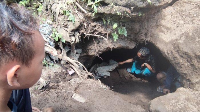 Seorang warga tengah menengok temuan kubur bilik di dekat rumah Wasit (43), Selasa (13/4/2021) (SURYA.CO.ID/DANENDRA KUSUMAWARDHANA )
