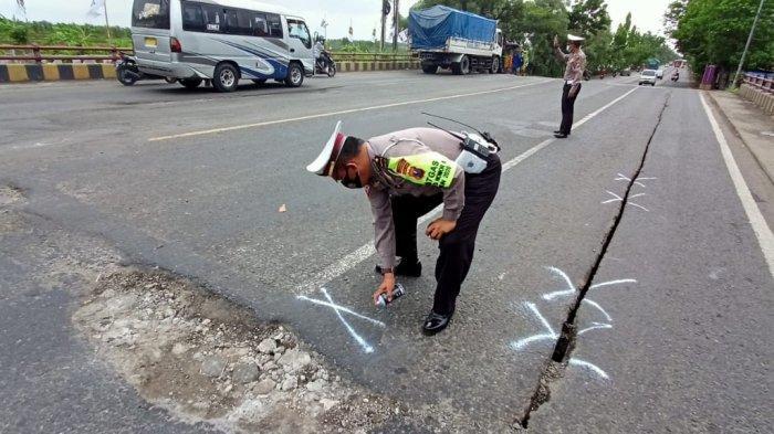Kanit Patroli, Ipda Fifin Y menandai sejumlah permukaan jalan dan jembatan yang rusak mengancam para pengguna jalan, Senin (14/12/2020).