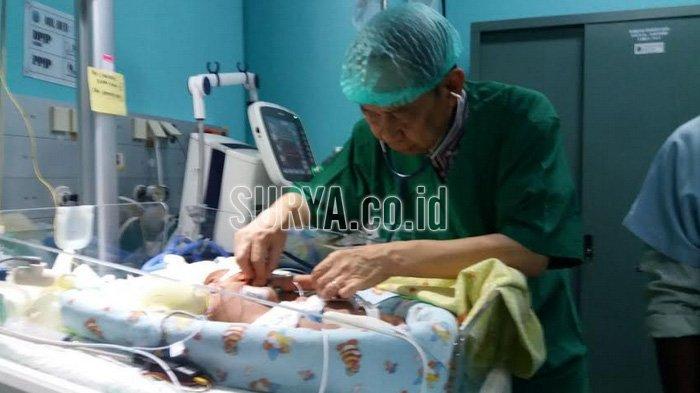 Ketua Tim Pusat Penanganan Kembar Siam Terpadu RSUD Dr Soetomo, Dokter Agus Harianto SpA (K) saat memantau kondisi bayi kembar siam Gedung Bedah Pusat Terpadu (GBPT) Rumah Sakit Umum Daerah Dr Soetomo, Kamis (12/4/2018).