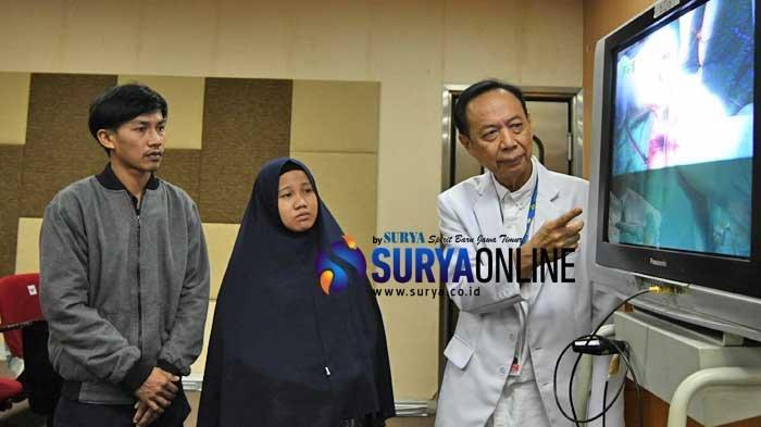 Ketua Tim Penanganan Kembar Siam RSUD Dr Soetomo, dr Agus Harianto, menjelaskan proses operasi kepada Silvina Dewi (19) (kiri), ibunda Aqila dan Azila kembar siam asal Kendari, Sulawesi Tenggara, ditemani suaminya Jasirin (25) lewat layar monitor di di Gedung Bedah Pusat Terpadu (GBPT), Rabu (14/8/2019).