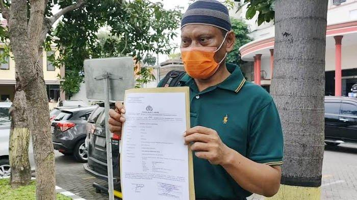 Ayah Korban menunjukkan surat tanda bukti laporan polisi usai mendampingi putrinya diperiksa atas kasus dugaan pencabulan di Mapolrestabes Surabaya, Rabu (3/3/2021). (SURYA.CO.ID/Firman Rachmanudin)