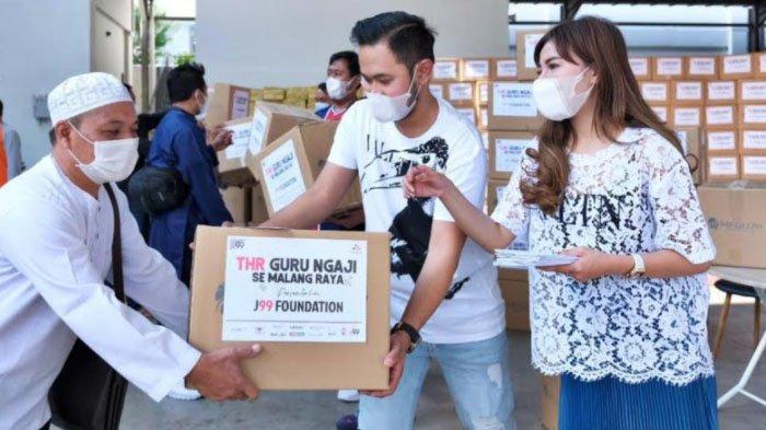Owner Juragan 99 Trans, Gilang Widya Pramana bersama sang istri, Shandy Purnamasari membagikan THR kepada para guru ngaji di Kota Malang.