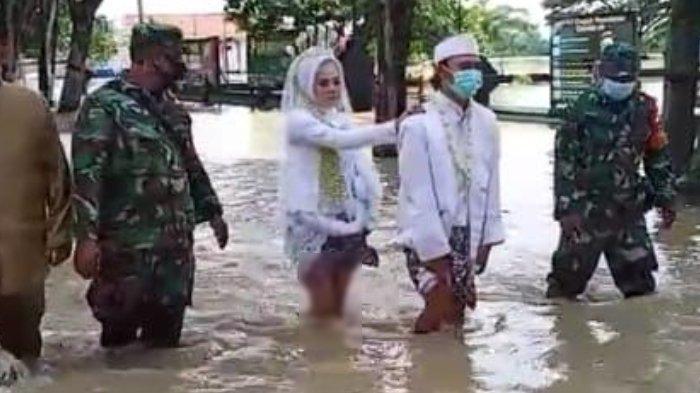 Pengantin jalan kaki terjang banjir di Jalan Raya Benjeng, Kabupaten Gresik, Senin (28/12/2020).