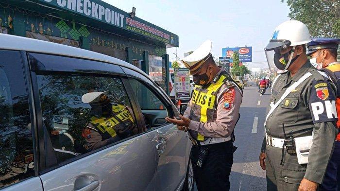 Petugas gabungan memeriksa kendaraan yang melintas di depan pos penyekatan Waru, Sidoarjo, Minggu (9/5/2021).
