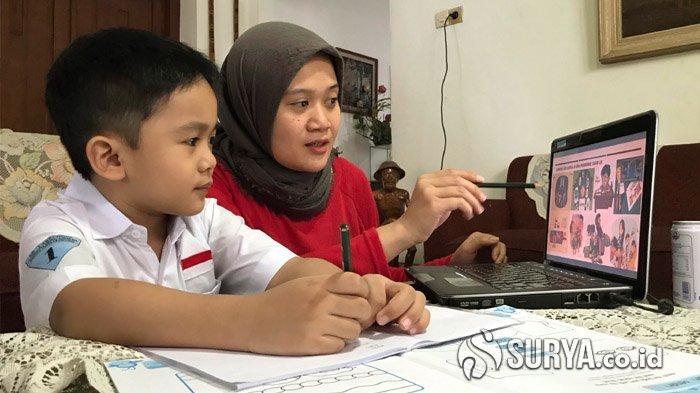 Orang tua dan anak saat melakukan kegiatan belajar jarak jauh atau online pada masa pembelajaran baru d itengah pandemi Covid-19, Jalan Ciliwung Surabaya, Rabu (15/7/2020).
