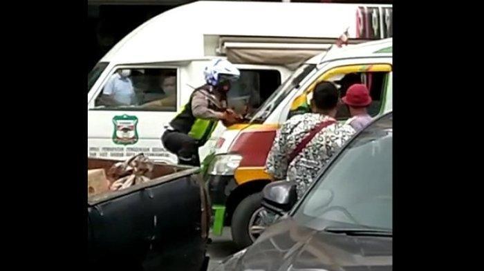 Foto: Tangkapan layar seorang Polantas menggantung diatas Angkutan umum di Jalan Sutomo Pematangsiantar, Senin (15/9/2020).