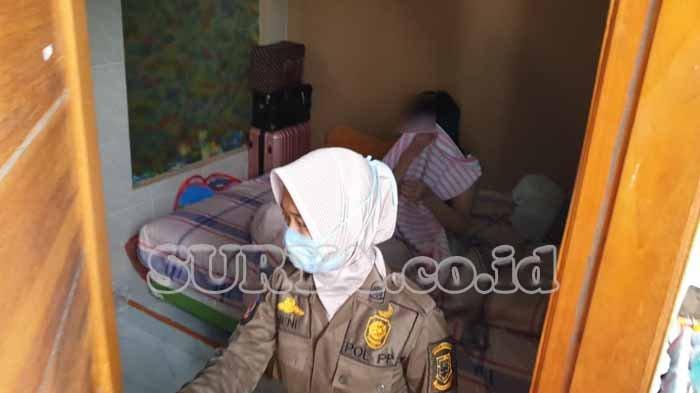 Seorang wanita Sidoarjo ini panik dan langsung menutupi badannya dengan selimut saat petugas Satpol PP Mojokerto Kota menggerebeknya, Senin (30/11/2020).