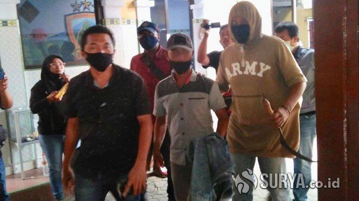 AS (tengah), suami yang bacok selingkuhan istrinya saat digiring polisi menuju ruang pemeriksaan, Selasa (13/10/2020).