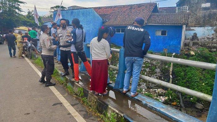 surya/sri wahyunik Warga dan anggota Polsek Silo mengawasi jembatan di atas sungai di sebelah Balai Desa Sempolan, Kecamatan Silo Jember, setelah seorang pria dilaporkan terjun ke sungai itu, Selasa (23/2/2021) siang