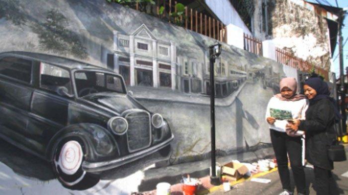 Warga melintasi mural pertokoan Kayutangan di Kampoeng Heritage Kajoe Tangan, Kota Malang.