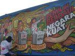 pelukis-menyelesaikan-mural-bertema-pemilu-2019-di-jalan-pemuda-surabaya.jpg