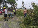 petugas-dari-polsek-benjeng-bersama-warga-memindahkan-pohon-tumbang.jpg