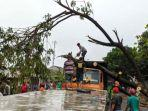 petugas-dibantu-warga-memotong-pohon-yang-roboh-ke-jalan-akibat-angin-kencang.jpg