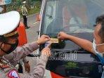 petugas-memasang-stiker-di-kendaraan-angkutan-di-pos-penyekatan-trenggalek-ponorogo.jpg