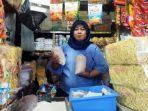 seorang-pedagang-sembako-di-pasar-wonokromo-surabaya-rahayu-menunjukkan-gula-pasir.jpg