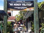 warga-melintas-di-bawah-gapura-anti-politik-uang.jpg