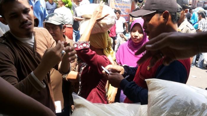 Sejumlah warga berusaha membeli beras murah dengan kupon palsu, dalam operasi Pasar yang digelar Pemkot Malang, Sabtu (28/2/2015).