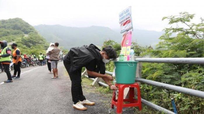 Salah satu pengunjung mencuci tangan sesuai Prokes di lokasi Wisata Gunung Kelud Kabupaten Kediri yang dilakukan uji coba pembukaan sejak Sabtu (10/4/2021)