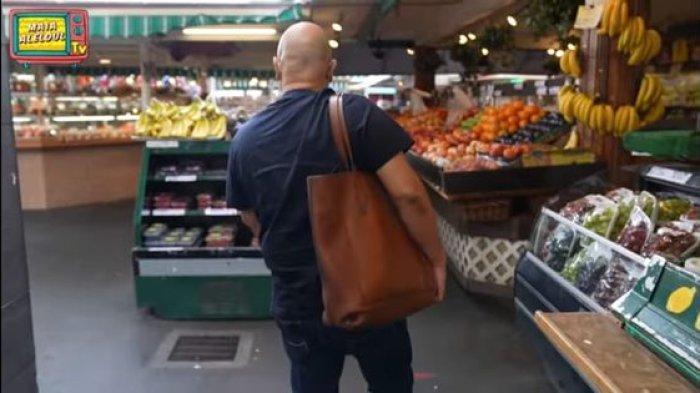 Gaya Irwan Mussry saat membawakan tas Maia Estianty ketika belanja