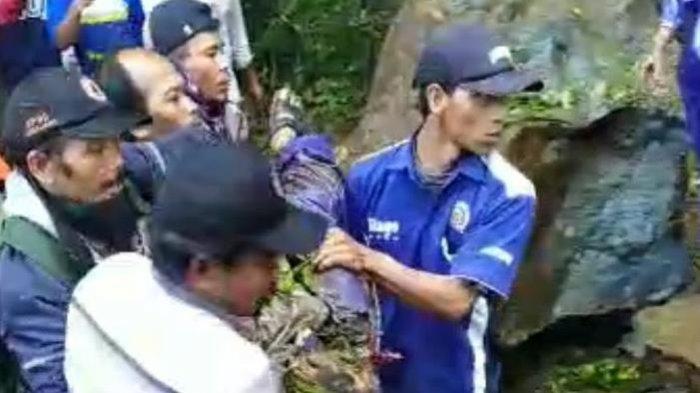 Tangkapan layar video warga saat mengevakuasi jenazah yang tertimpa batu karena terkena longsor di sejumlah titik jalur perbukitan Piket Nol, Desa Sumberwuluh, Kecamatan Candipuro, Lumajang, Sabtu (10/4/2021).