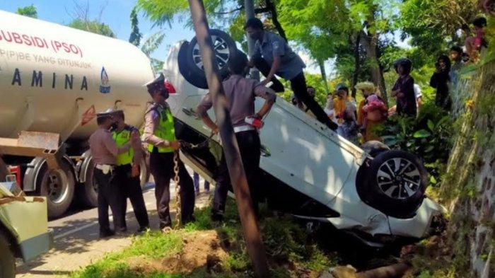 Pengemudi Diduga Mengantuk, Honda Brio Tabrak Pemotor Lalu Terbalik Masuk Selokan di Jember