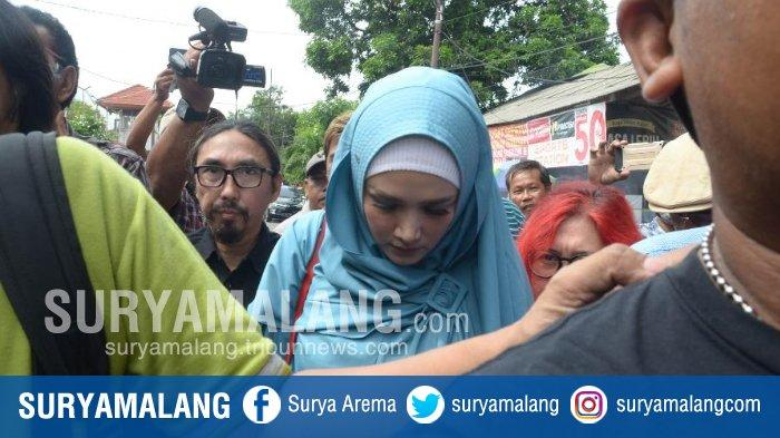 Istri musisi dan politikus Ahmad Dhani, Mulan Jameela (berhijab biru muda) saat menjenguk suaminya di Rutan Medaeng, Sidoarjo, Senin (11/2/2019).