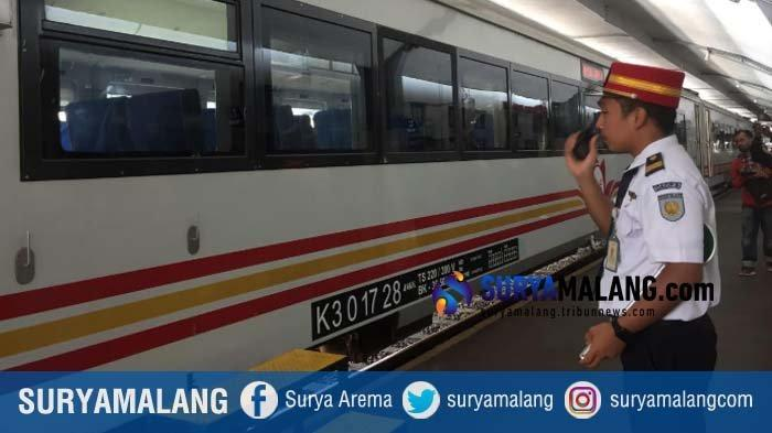 Seorang petugas di Stasiun Malang sedang mengatur perjalanan kereta api