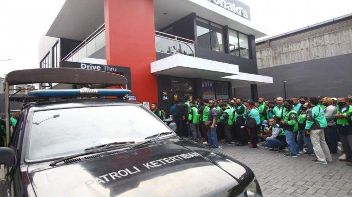 Polisi mengatur ratusan Ojol mengantre membeli orderan McD BTS Meal di Gerai McDonald's Jalan Sunandar Priyo Sudarmo, Kota Malang, Rabu (9/6/2021).