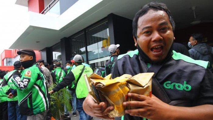 Ekpresi pengemudi Ojol setelah mendapatkan McD BTS Meal di Gerai McDonald's Jalan Sunandar Priyo Sudarmo, Kota Malang, Rabu (9/6/2021).