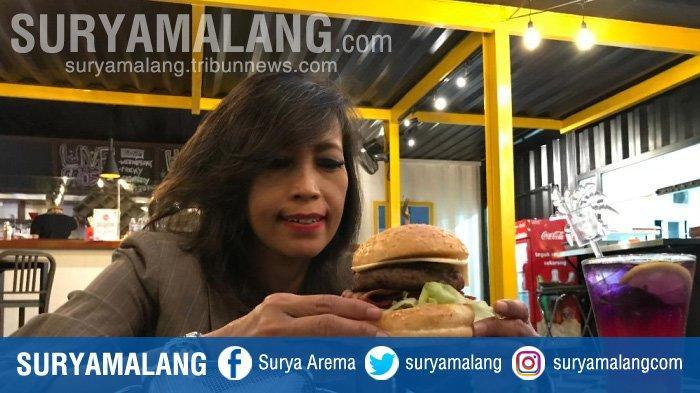 Pengunjung saat menyantap Monster Burger yang menjadi menu andalan di Kafe Tengah Kota Surabaya, Rabu (16/9/2020).