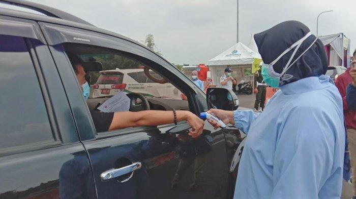 Suasana pemeriksaan suhu tubuh pengendara di Exit Tol Madyopuro Kota Malang, Kamis (6/5/2021).