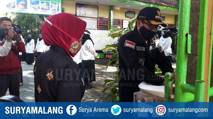 Walikota Malang Sutiaji memberi contoh cuci tangan saat masuk area SMPN 8 Kota Malang saat dilakukan simulasi tatap muka terbatas di sekolah itu beberapa waktu lalu.