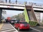 bak-truk-tronton-nopol-s-8218-ur-tersangkut-jembatan-layang-penyeberangan-di-tol-sidoarjo-porong.jpg
