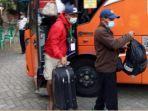 pekerja-migran-turun-dari-bus-jemputan-yang-disiapkan-pemkab-tulungagung.jpg