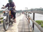 pengendara-sepeda-motor-menyeberangi-jembatan-kayu-di-atas-waduk-saguling-bandung.jpg
