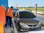 petugas-membantu-pengemudi-kendaraan-yang-akan-melintas-di-gerbang-tol-madiun.jpg