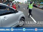 petugas-memberhentikan-kendaraan-yang-akan-masuk-wilayah-kabupaten-malang.jpg