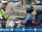 petugas-menegur-pengendara-yang-tidak-memakai-helm-di-persimpangan-puntodewo-kota-malang.jpg