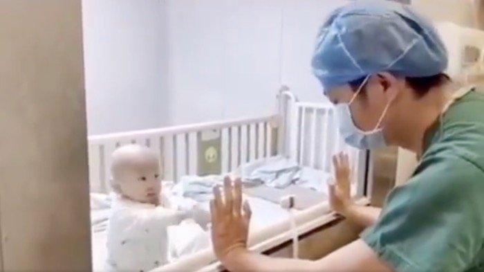 Viral Video Bayi Terinfeksi Virus Corona Bercanda dengan Ayahnya Lewat Kotak Kaca & Tak Bisa Dipeluk