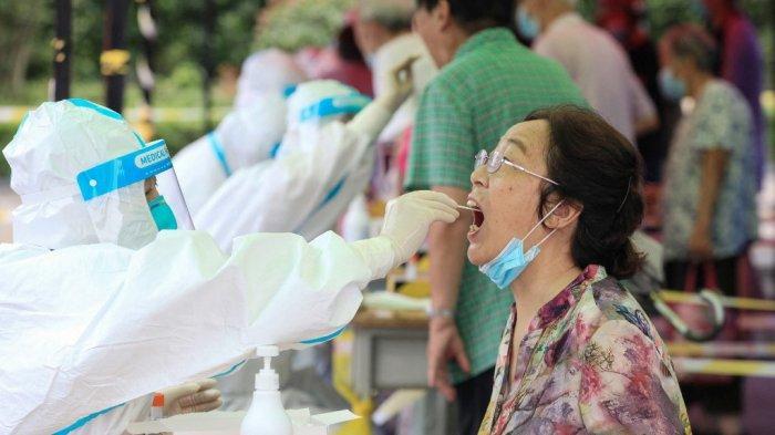 Seorang wanita menerima tes asam nukleat untuk virus corona Covid-19 di Nanjing, di provinsi Jiangsu timur pada 29 Juli 2021.