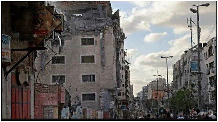 Sejumlah warga Palestina berkumpul di dekat gedung kantor Bulan Sabit Merah Qatar di Kota Gaza yang terkena serangan udara Israel pada Senin (17/5/2021).