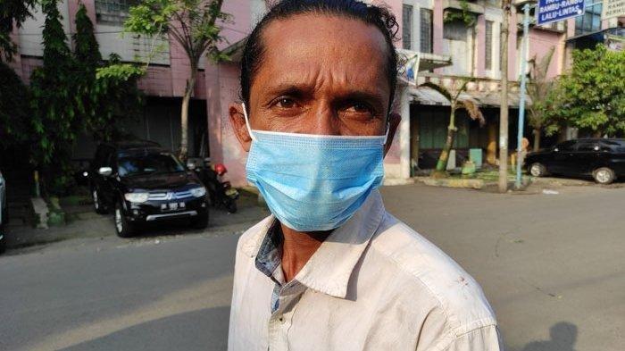 Seorang tukang parkir bernama Holmes Manulang pasrah saat didenda Rp 100 ribu. Pria tersebut didenda karena tak menggunakan masker.